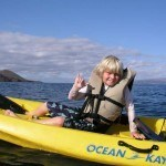 Boy giving shaka on kayak